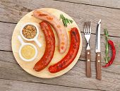 foto of condiment  - Various grilled sausages with condiments on cutting board - JPG