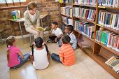 foto of pupils  - Cute pupils and teacher having class in library at the elementary school - JPG