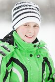 stock photo of cold-shoulder  - Cold young boy in winter clothes sprinkled with fresh snow smiling at the camera as he enjoys a day outdoors in a wintry landscape - JPG