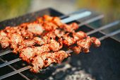 stock photo of souvlaki  - Grilled marinated caucasus barbecue meat shashlik shish kebab pork meat grilling on metal skewer