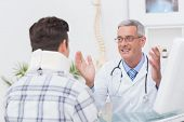 pic of neck brace  - Doctor talking to patient wearing neck brace in medical office - JPG