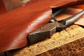 image of leather tool  - Leather belt and nippers on table close up - JPG