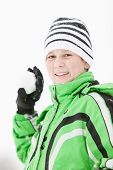 stock photo of snowball-fight  - Smiling young boy in winter gloves green jacket and knitted beanie cap preparing to throw a snowball at the camera - JPG