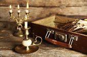 pic of old suitcase  - Old wooden suitcase with old books on wooden background - JPG