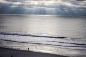 image of atlantic ocean beach  - Sunbeams illuminate  the Atlantic Ocean horizon with a single tourist in the foreground - JPG