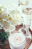 stock photo of copper  - Bouquet of white flowers in a vase, candles and champagne on a copper tray vintage, wedding home decor