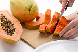 pic of papaya fruit  - Halved papaya fruit being cut into slices with a sharp kitchen knife on a wooden cutting board - JPG