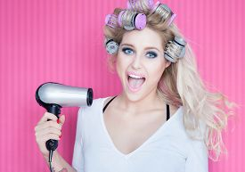 picture of hair blowing  - Young attractive happy laughing blonde woman with hair dryer and rollers - JPG