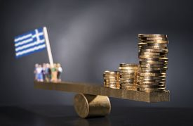 stock photo of seesaw  - Seesaw with coins on one side and a group of people with the Greek flag on the other side - JPG