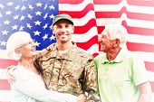 picture of reunited  - Soldier reunited with parents against rippled us flag - JPG