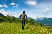 picture of bavarian alps  - Rear view of a male tourist standing on a grassy plateau enjoying the scenic Bavarian alps in the Berchtesgaden National Park - JPG