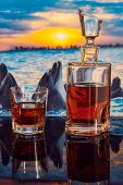 stock photo of dolphins  - bottle of whiskey on a background of dolphins swim at sunset - JPG