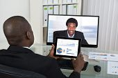 stock photo of video chat  - Businessman With Digital Tablet Video Chatting With Male Colleague On Computer In Office - JPG