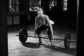 stock photo of jerks  - Black And White Shot Of Woman Preparing to Lift Weights - JPG
