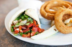 stock photo of sandwich wrap  - Chicken pita wrap sandwich with onion rings and a deli pickle slice - JPG