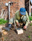 picture of lavabo  - an asian man whets a scythe with a hammer - JPG