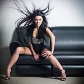 The beautiful woman sitting on a leather sofa