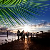 silhouetted  people walking on street over sunset sky with sunbeam  poster