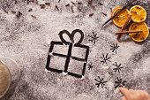Child hand drawing christmas present and twinkling stars in the flour spread to make cookies poster