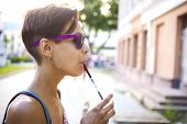 A Girl Drinks A Drink Through A Straw. A Woman In Glasses Drinks Morning Coffee On A City Street. A  poster