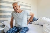 Senior man suffering from back pain at home while wife sleeping on bed. Old man with backache having poster