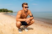 fitness, sport and technology concept - tired male runner with earphones and smartphone in arm band  poster