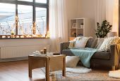 interior, christmas and interior concept - cushioned sofa, coffee table, garland string and candles  poster