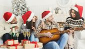 New Year Celebration Party. Man Playing On Guitar For Friends At Christmas House Party, Copy Space poster