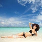 stock photo of tropical island  - Happy fashion woman rest on the beach - JPG