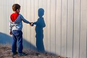 Boy And His Shadow. Lonely Little Child Playing With His Shadow Outside. Imaginary Friend. The Conce poster