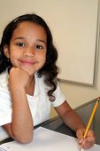 picture of young girls  - Young Girl at Her School Writing With a Pencil - JPG