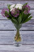 Fresh Flowers In Glass Vase. Bouquet Of White Chrysanthemum And Purple Allium On Wooden Background.  poster