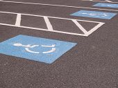 image of physically handicapped  - A painted wheelchair symbol by a handicapped parking area - JPG