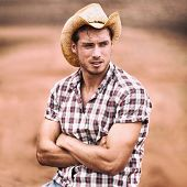 Cowboy hat sexy handsome american man in USA countryside farm. Farmer in plaid shirt serious looking poster
