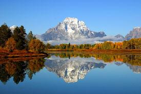 picture of mountain-range  - Reflection of mountain range in a lake at Grand Teton National Park - JPG