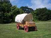 stock photo of tarp  - Antique western wagon with original wheels and tarp showing beautiful green grass trees and blues sky in eastern connecticut usa - JPG