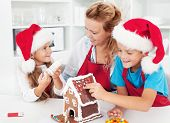 stock photo of gingerbread house  - Making a gingerbread cookie house with the kids at christmas time - JPG