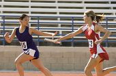 stock photo of relay  - Female runners passing baton in relay race - JPG