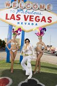 Elvis impersonator with casino dancers in front of a 'Welcome to Las Vegas' sign