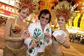 Elvis impersonator standing with casino dancers