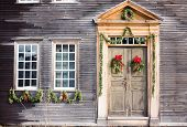 stock photo of christmas wreaths  - Christmas wreaths and garlands decorating an old wood house - JPG