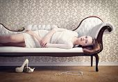 stock photo of seductress  - Beautiful young woman relaxing on a vintage sofa - JPG