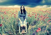 Mysterious portrait of young beautiful woman sitting on stool in a poppy field and looking at camera
