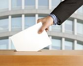 image of democracy  - Hand putting a voting ballot in a slot of box - JPG