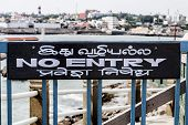 image of kanyakumari  - a wooden sign affixed above a wooden gate shows in English and Asian language the prohibition of entry to a path - JPG