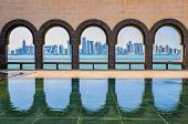 stock photo of qatar  - Doha skyline seen through the arches at the Museum of Islamic art Doha Qatar - JPG