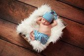 stock photo of sleeping  - Newborn baby sleeping in a wooden crate on faux fur wearing blue and white striped pajamas with matching sleeping cap - JPG