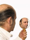 stock photo of inner ear  - a man looking in a mirror at his inner self - JPG