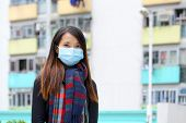 image of swine flu  - Woman wearing medical face mask in crowded city - JPG