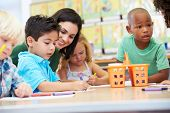 stock photo of teacher  - Group Of Elementary Age Children In Art Class With Teacher - JPG